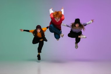 Group of teens, boys and girls dancing hip-hop in stylish clothes on gradient studio background in neon light.