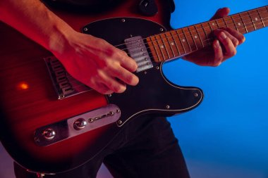 Young caucasian musician playing guitar in neon light on blue background, inspired