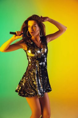 Caucasian female singer portrait isolated on gradient studio background in neon light
