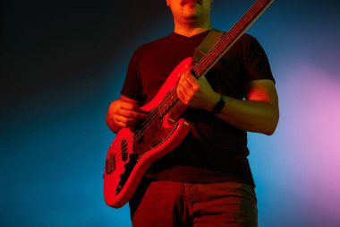 Young caucasian musician playing on gradient background in neon light. Concept of music, hobby, festival
