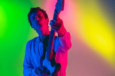Young caucasian musician, guitarist playing on gradient background in neon light. Concept of music, hobby, festival