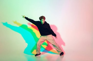 Young beautiful man dancing hip-hop, street style isolated on studio background in neon light
