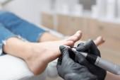 Fotografie Nahaufnahme des Arztes in Handschuhen, die Prozedur für Fuß mit speziellen elektrischen Geräten für den Kunden machen. Pflege von Füssen und Nägeln im Schönheitssalon. Podologie und medizinisches Konzept.