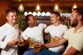 Fotografia Azienda di quattro uomini belli che tiene vetro di birra, sorridente e abbracciando.