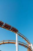 Fotografie Von unten hoch orange Achterbahn in Santa Monica Pier, Los Angeles, Kalifornien auf blauen Himmelshintergrund