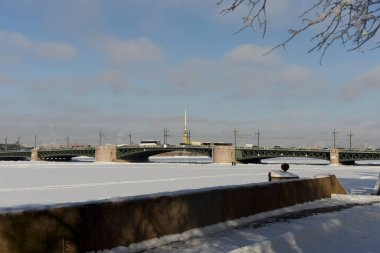 Winter view on Saint Petersburg, Russia, with Palace Bridge, rostral column, Peter and Paul Cathedral in the Fortress and the Neva river covered by ice and snow.