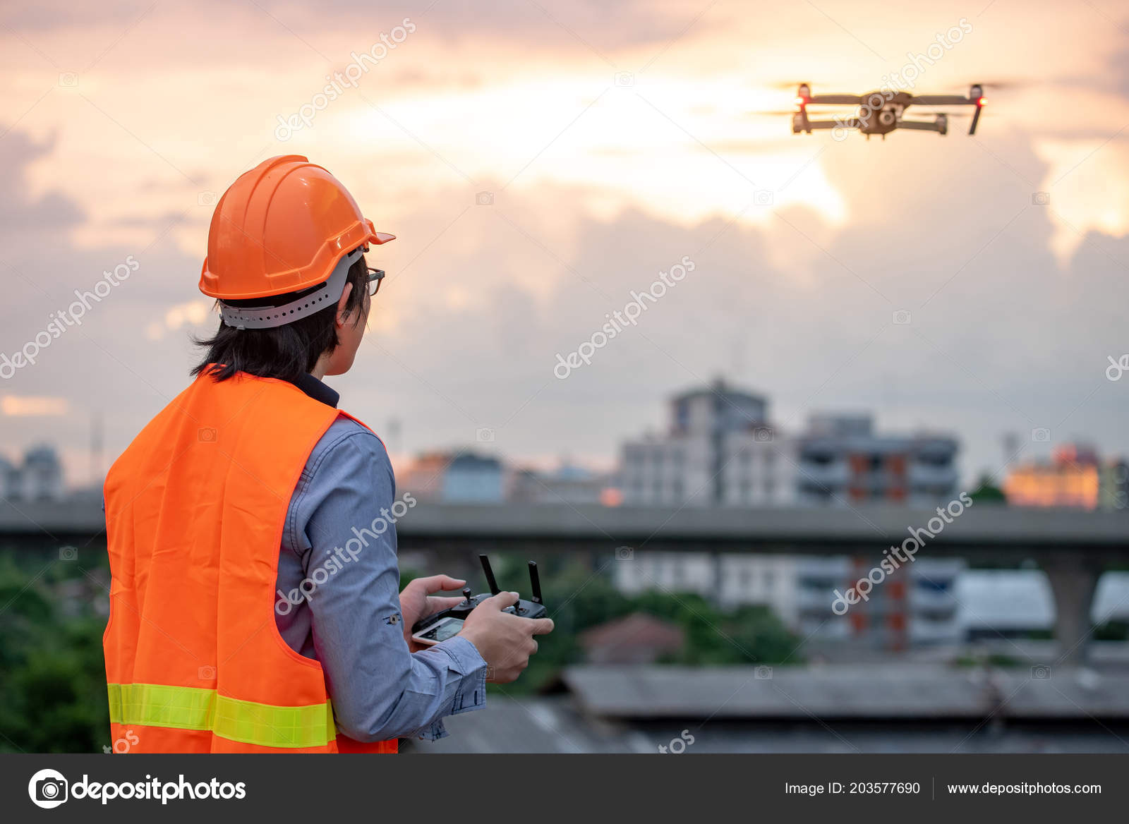 Young Asian Engineer Flying Drone Construction Site Sunset Using