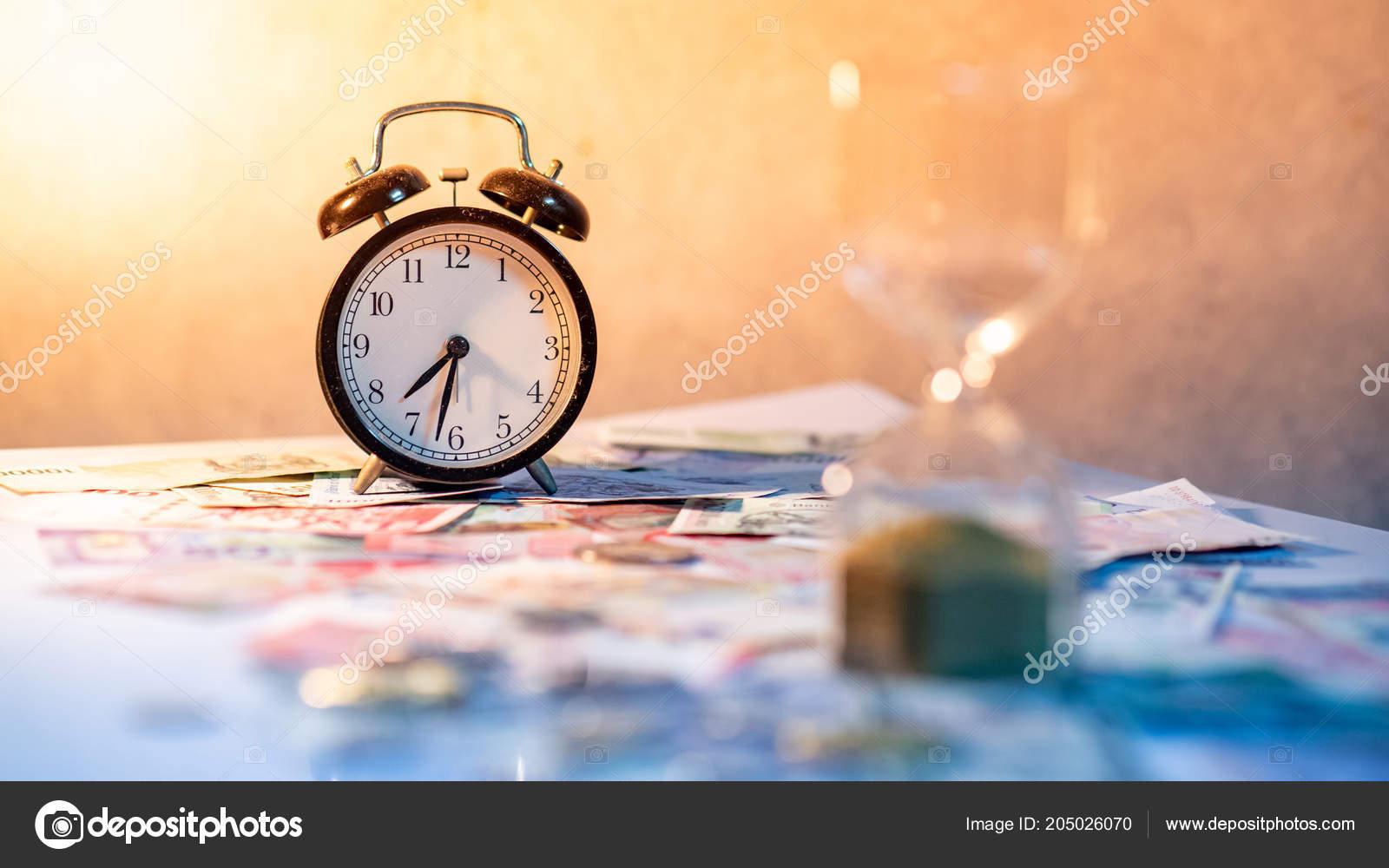 c607c6a80c5 Reflexo do relógio e turva ampulheta na mesa brilhante com notas e moedas  da moeda internacional. Tempo de investimento e passagem de tempo.