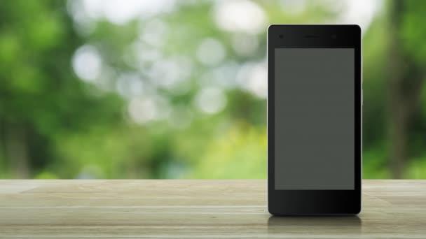 E-Mail-Flaches Symbol auf modernen Smart-Handy-Bildschirm auf Holztisch über Unschärfe grünen Baum im Park, Business-Kommunikation Online-Konzept