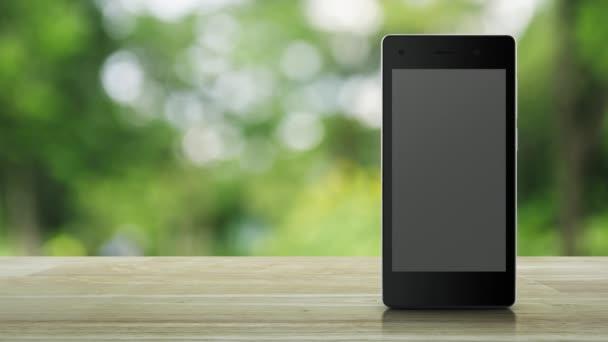 Bank lakás ikon a modern intelligens mobiltelefon képernyőjén a fából készült asztal alatt blur zöld fa a parkban, mobil banki koncepció
