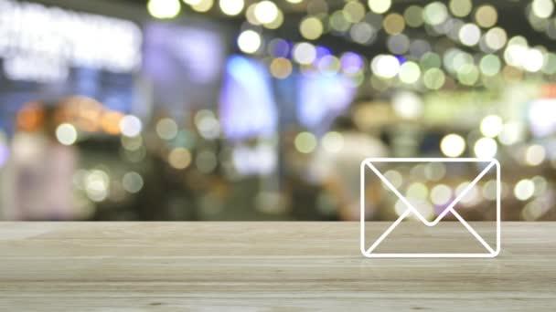 emailová ikona na dřevěném stole přes světlo rozostření a stín nákupního střediska, firemní kontakt online koncepce