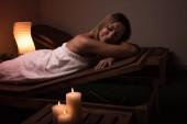 Masáž. Krásná dívka ve spa salonu se svíčkami