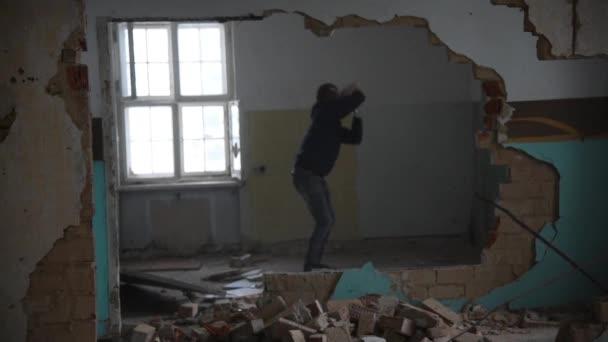 Depressziós és őrült ember dob kövek egy régi, elhagyatott ház