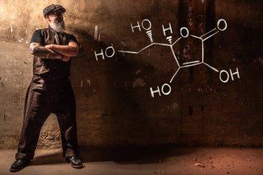 Bearded old man presenting handdrawn chemical formula of Vitamin C