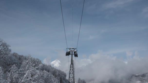 Légifelvételek havas hegy gerincen völgyre, felhők, felvonó emelés. Szabadtéri havas pusztaság természet turisztikai gondola szállítás télen. Magaslati kabinos felvonó télen. Sífelvonótól