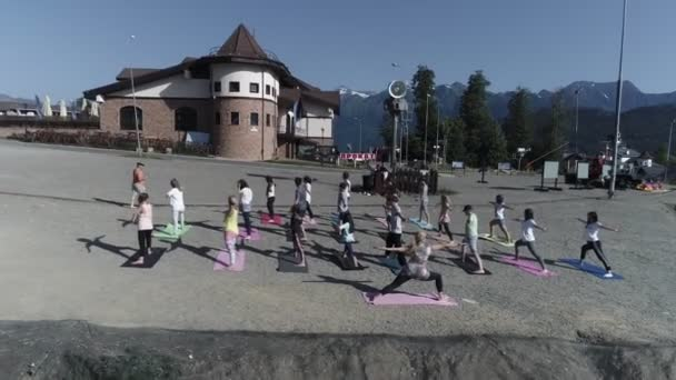 SOCHI, RUSSIA - MAY 2, 2018: Group of people do yoga at outdoor playground in sunny morning, wave hands. Blue sky. Green mountains. Trainer.