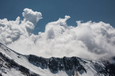 Aerial photography. Snow-capped mountains. Clouds in the blue sky. The top of the mountain Aibga, Sochi. Ski resort Krasnaya Polyana.
