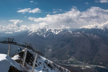 Cable car on top of Aibga mountain, in the village of Krasnaya Polyana, Sochi. Blue clear sky with clouds. Tourist season in the mountains.