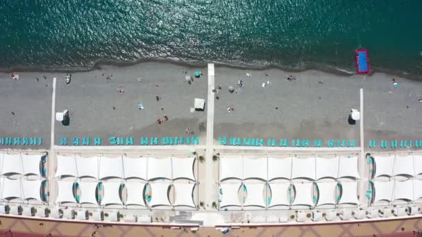 Aerial video shooting. Coastline. Recreation and swimming area. Equipped beach on the black sea in Sochi, Russia. Holiday season. Camera view down. Blue sea water. Flying along the shore.