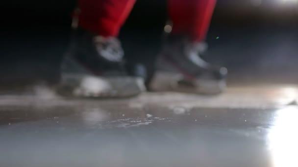 Hokejista se LED jiskry na vysokorychlostní brzdění ve tmě na aréně