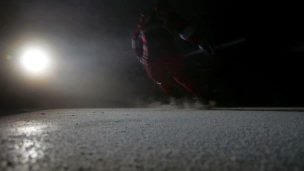 Hokejisté se LED jiskry na vysokorychlostní brzdění ve tmě na arena