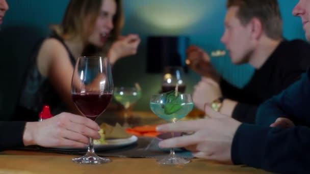 Freunde klimpern im Restaurant mit Wein und Cocktails
