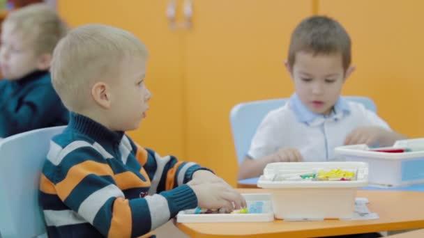 Děti hrají s plastovou stavební bloky ve školce