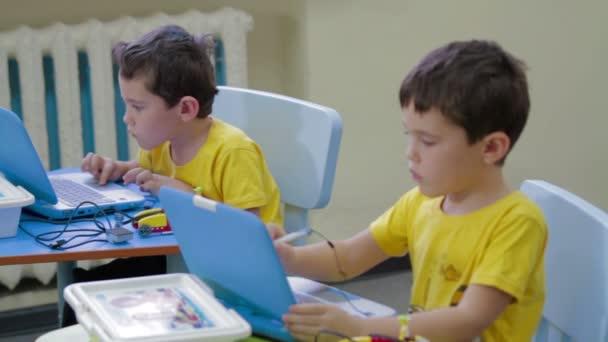 Kids typing on laptop at kindergarten