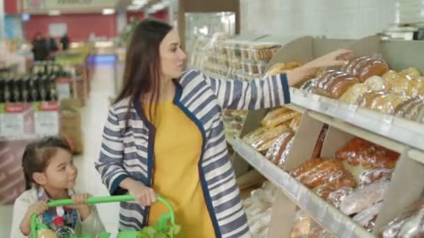 Žena a dcera nutnosti čerstvý chléb v supermarketu
