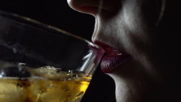Girl drinks whiskey from glass on black background. Blonde girl tasting cognac