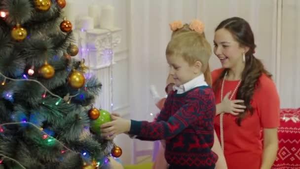 Matka a děti zdobí vánoční strom. Šťastná rodina