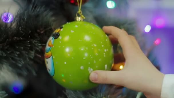 Putting ornament on Christmass tree