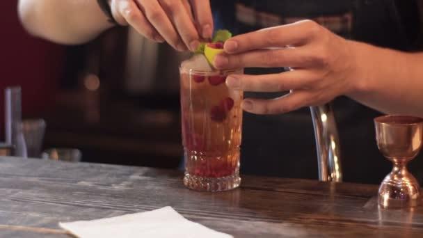 Professionelle Barkeeper cocktail mit Limette, Himbeere und Minze dekorieren