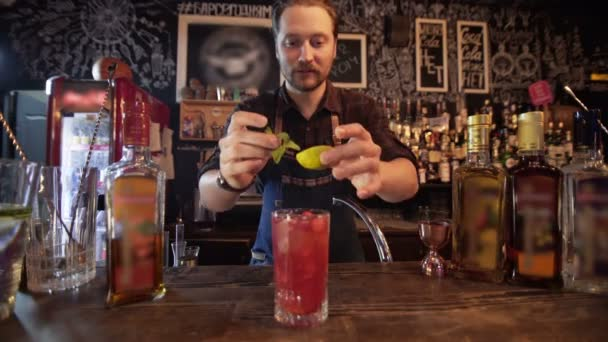 Professional bartender decorating cocktail with lime, raspberry and mint