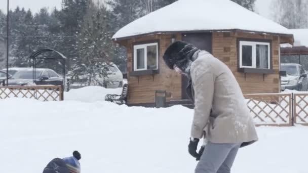 Junger Vater und Sohn wirft Schneebälle aufeinander. Familie Winter geniessen