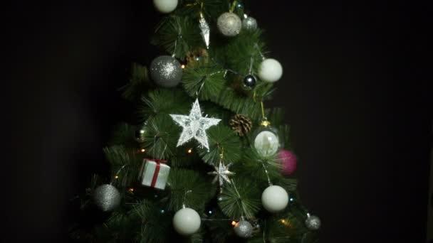 Vánoční koule a osvětlení na vánoční stromeček proti tmavým pozadím