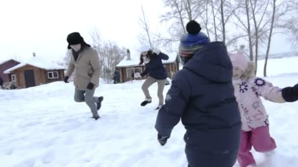 Mother, father and two children havinf fun in snow