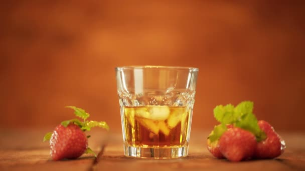 Alcoholic drink with ice cubes in cool glass and Strawberry on table