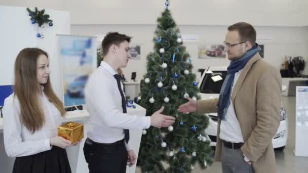 Men shaking hands in beautiful car dealership on background of christmas tree