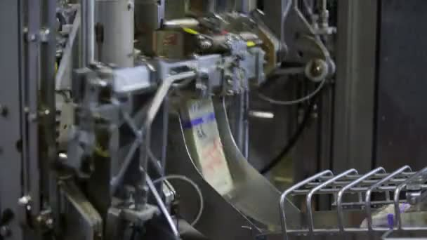 Milk packaging line. Dairy products in tetra packaging are moving along conveyor at a dairy factory