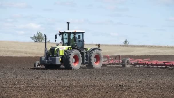 Tractor plows field with plows before sowing. Agricultural machinery on plowing field