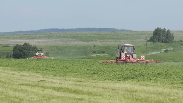 Farming tractors moving on agricultural field for harvesting land. Agricultural machinery on harvesting field