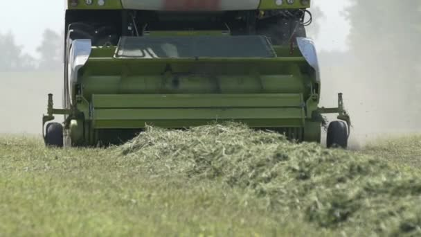 Combine harvester empties herbal in field on summers day