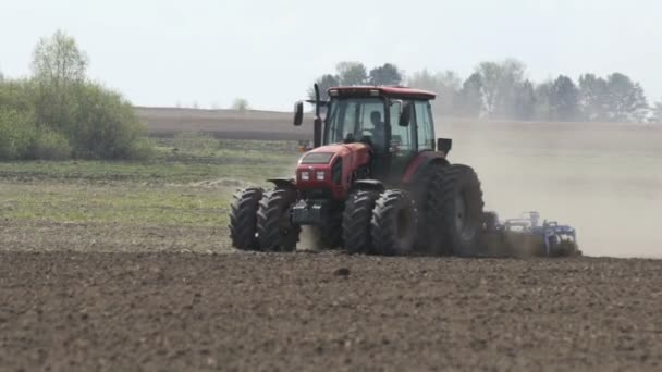 Slow motion shot of Farming tractor moving on agricultural field for plowing land. Agricultural tractor plowing field