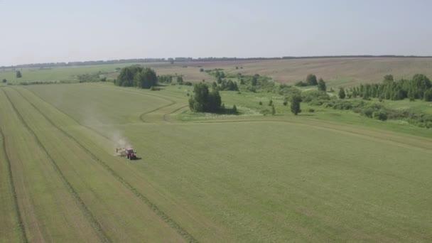 Trattore nuovo di zecca sul campo di lavoro. Campo di raccolta del trattore. Settore coltivatore trattore