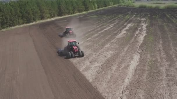 Brand new tractors on field working. Tractor plowing land. Tractor cultivating field