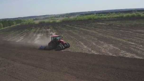 Mezőgazdasági traktor mozog a mezőgazdaság területén a szántás földet. Mezőgazdasági traktor szántás gazdálkodás területén