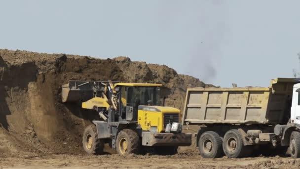 Bulldozer nakládací vůz na staveniště. Stavební vybavení. Prohledávač buldozer pohybující se písek.