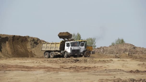 Planierraupe belädt Sandtransporter auf Baustelle. Baumaschinen. Planierraupe bewegt Sand.