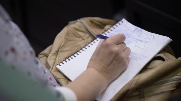 Nahaufnahme von Händen, die Stifte halten und Notizen auf der Konferenz machen